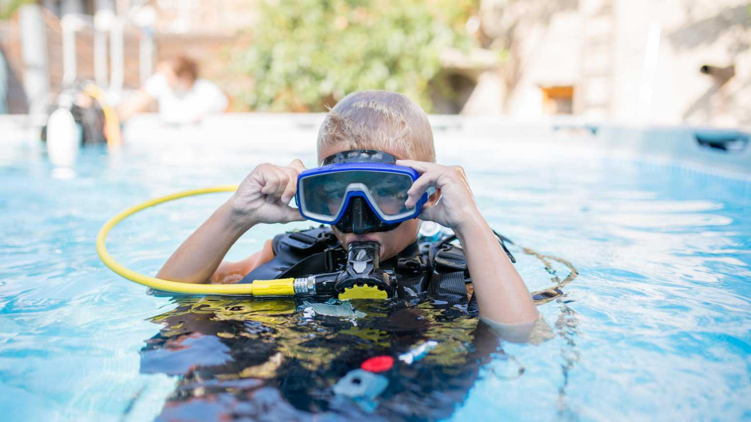Child scuba diving in pool
